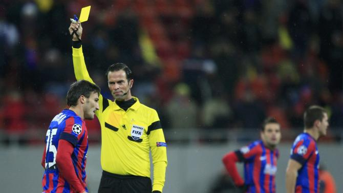 Referee Nijhuis shows a yellow card to Steaua Bucharest's Piovaccari during their Champions League soccer match against Schalke 04 in Bucharest
