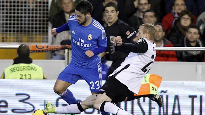 Real Madrid's Francisco Alarcon Isco duels for the ball with Valencia's Jeremy Mathieu from France during their La Liga soccer match at the Mestalla stadium in Valencia, Spain, Sunday, Dec. 22, 2013
