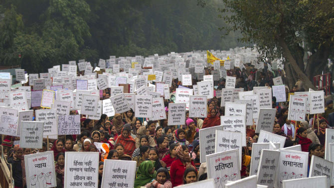 """Indian women carry placards as they march to mourn the death of a gang rape victim in New Delhi, India, Wednesday, Jan. 2, 2013. India's top court says it will decide whether to suspend lawmakers facing sexual assault charges as thousands of women gathered at the memorial to independence leader Mohandas K. Gandhi to demand stronger protection for their safety. The banners read """"India won't tolerate women's insult and We want respect not violence in life."""" (AP Photo/ Dar Yasin)"""