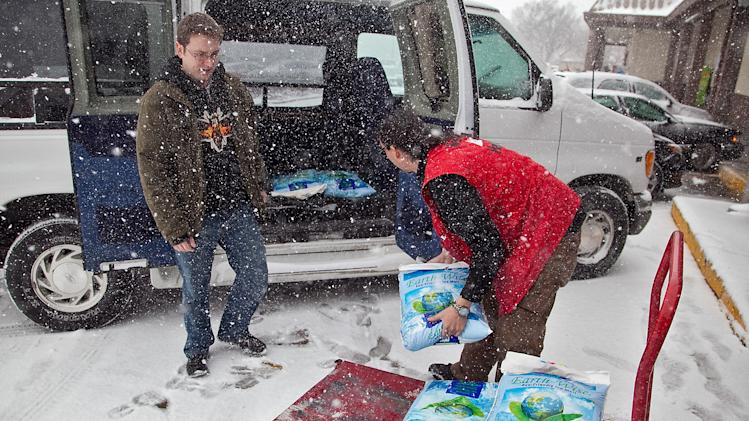 Westlake Ace Hardware employee Kenneth Curiel, right, helps customer Marcus Dunn load six 40-pound bags of ice melt into this van in Wichita, Kan. Wednesday, Feb. 20, 2013. (AP Photo/The Wichita Eagle, Mike Hutmacher)