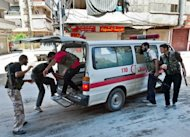 "Syrian rebel fighters load a wounded person into an ambulance during clashes with Syrian government forces in the al-Sahur district in Aleppo. President Bashar al-Assad vowed on Tuesday to crush the 17-month rebellion against his regime and to cleanse Syria of ""terrorists,"" as his troops engaged rebels in key battleground city Aleppo"