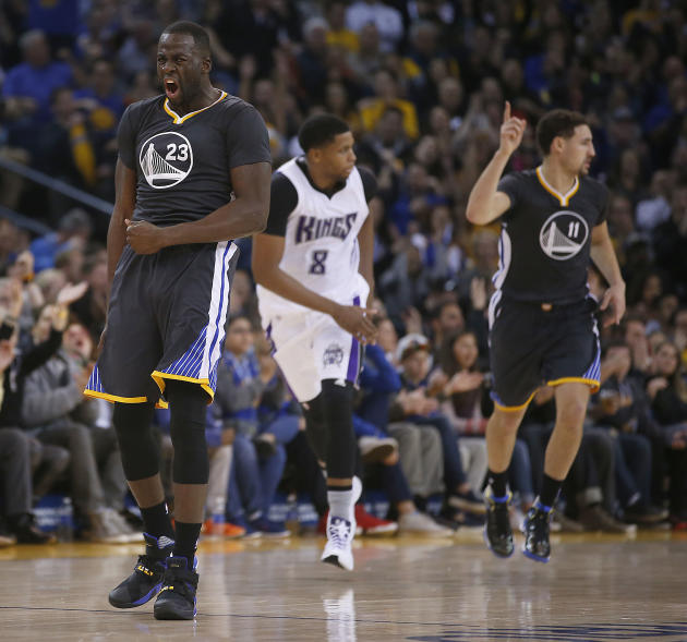 Golden State Warriors forward Draymond Green (23) reacts after guard Klay Thompson, right, hit a three-point shot against Sacramento Kings forward Rudy Gay, center, during the first half of an NBA bas