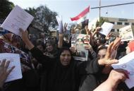 """Egyptian women supporting the army hold booklets of Egyptian constitution drafts saying """"Yes"""", and dance as they hold pictures of army chief General Abdel Fattah al-Sisi, beside a polling station in Cairo, January 15, 2014. REUTERS/Mohamed Abd El Ghany"""