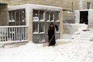 A Palestinian woman shovels in front of a building after heavy snowfall on January 10, 2013 in Tuqua, near the West Bank City of Bethlehem. The worst storms in a decade left swathes of Israel and Jordan under a blanket of snow and parts of Lebanon blacked out on Thursday, bringing misery to a region accustomed to temperate climates