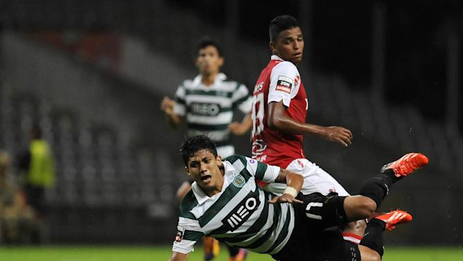 Sporting's Fredy Montero, front, from Colombia, is tackled by Sporting Braga's Aderlan Santos, from Brazil, during their Portuguese League soccer match at the Municipal Stadium, in Braga, Portugal, Saturday Sept.. 26, 2013
