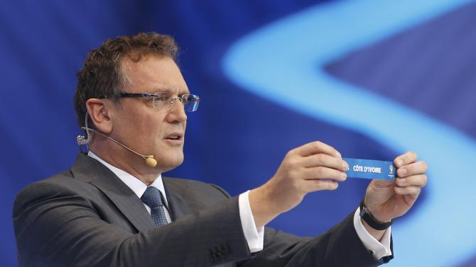 "Valcke holds up the slip showing ""Ivory Coast"" during the draw for the 2014 World Cup in Sao Joao da Mata"