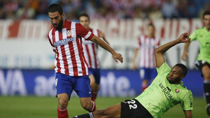 Atletico Madrid's Turan challenges for ball with Osauna's Loties during Spanish first division soccer match in Madrid