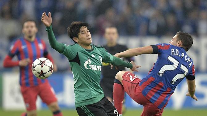 Schalke's Atsuto Uchida, left, challenges for the ball with Bucharest's Adrian Popa, right, during the Champions League Group E soccer match between FC Schalke 04 and Steaua Bucharest  in Gelsenkirchen, Germany, Wednesday, Sept. 18, 2013