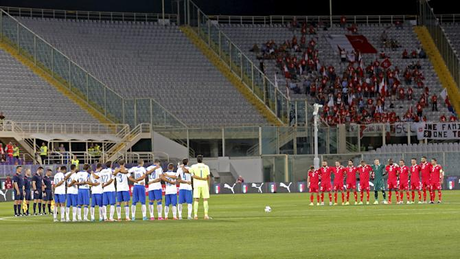Italy and Malta players pause to pay their respects for the victims of Europe's migrant crisis before their Euro 2016 qualification match at the Franchi stadium in Florence