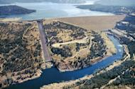 This June 23, 2005, aerial photo provided by the California Department of Water Resources shows Oroville Dam, Lake Oroville and the Feather River in the foothills of Sierra Nevada near Oroville, Calif. The concrete spillway that was undermined and developed huge holes in the last few days is at lower left. Release of water from the dam, the damaged spillway and the use of an earthen emergency spillway has caused a temporary evacuation on Sunday, Feb. 12, 2017, of thousands of people downstream. (Paul Hames/California Department of Water Resources via AP)