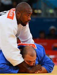 France's Teddy Riner (white) competes with Tunisia's Faicel Jaballah (blue) during their men's +100kg judo contest match of the London 2012 Olympic Games on August 3, 2012 at the ExCel arena in London. AFP PHOTO / MIGUEL MEDINA