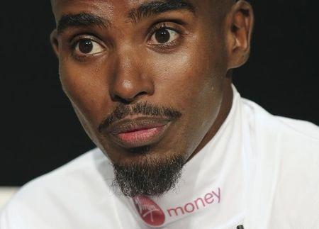 Farah reacts during a news conference ahead of competing in this year's London marathon, central London