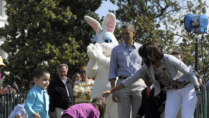 President Barack Obama and first lady Michelle Obama watch as children participate in the annual Easter Egg Roll on the South Lawn of the White House in Washington, Monday, April 1, 2013. (AP Photo/Susan Walsh)