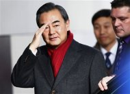 Chinese Minister of Foreign Affairs Wang Yi waves on his arrival at the Intercontinental hotel where talks are being held in Geneva November 23, 2013. REUTERS/Denis Balibouse