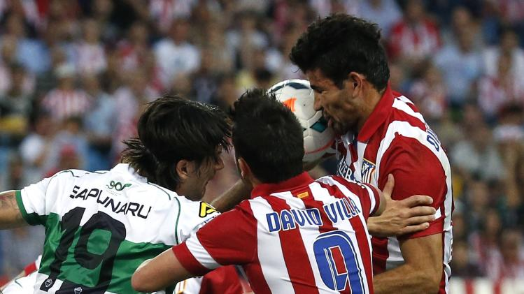 Atletico Madrid's Costa and Elche's Sapunaru fight for the ball next Atletico Madrid's Villa during their Spanish first division soccer match at Vicente Calderon stadium in Madrid