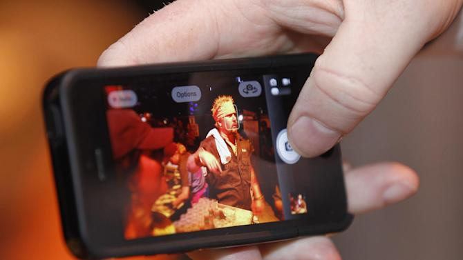 Guy Fieri is seen  on a cell phone at the South Beach Wine and Food Festival's Burger Bash, Friday, Feb. 22, 2013, in Miami Beach, Fla. (AP Photo/Luis M. Alvarez)