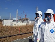 Japanese workers stand near the stricken Fukushima nuclear plant in Okuma. The operator of the crippled Fukushima nuclear plant admitted it had played down the risks of a tsunami to the facility for fear of the financial and regulatory costs.