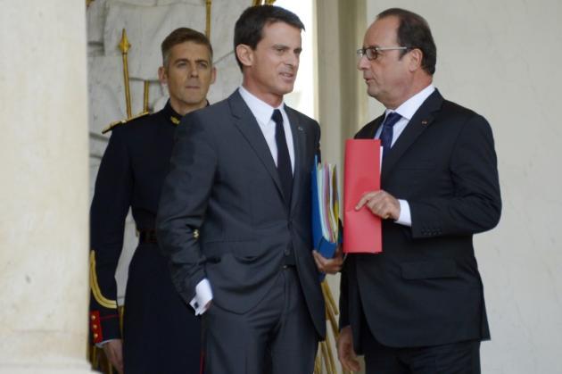 Le président français François Hollande (d) et son Premier ministre Manuel Valls (c) sur le perron de l'Elysée à Paris, le 23 septembre 2015