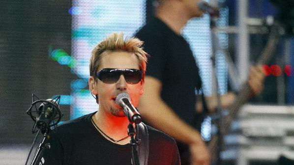 FILE - In this Nov. 24, 2011 file photo, Nickelback lead vocalist Chad Kroeger and his band perform during halftime at an NFL football game between the Detroit Lions and the Green Bay Packers in Detroit.  A spokeswoman for pop singer Avril Lavigne confirmed a Tues., Aug. 21, 2012 report from People.com that Lavigne and Chad Kroeger were engaged earlier this month after a six-month courtship.   (AP Photo/Rick Osentoski, file)