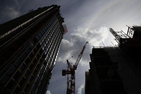 A crane is silhouetted at a construction site in central London July 2, 2014. REUTERS/Luke MacGregor