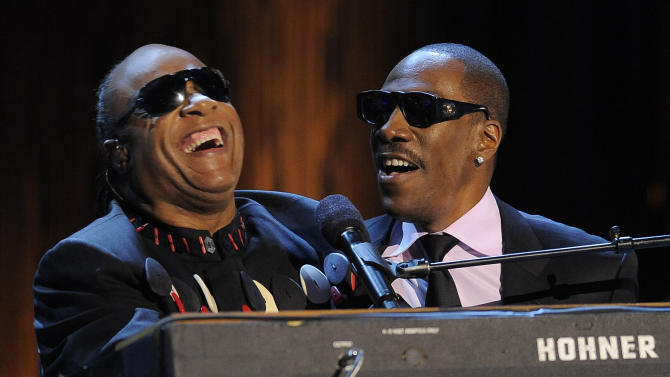 """Stevie Wonder, left, is joined by Eddie Murphy to sing Wonder's song """"Higher Ground"""" onstage during """"Eddie Murphy: One Night Only,"""" a celebration of Murphy's career at the Saban Theater on Saturday, Nov. 3, 2012, in Beverly Hills, Calif. (Photo by Chris Pizzello/Invision)"""