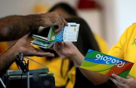 A salesman delivers tickets to a sports fan at the 2016 Rio Olympics ticket office in Rio de Janeiro
