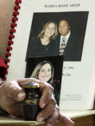 In this photo taken Aug. 4, 2011 at his home in Tagaytay City, south of Manila, Philippines, Rudy Abad holds a small urn in which he keeps a portion of ashes of his wife Marie Rose Abad, shown in photos in background, who died during the Sept. 11 2001 World Trade Center terrorist attacks in New York City. Unlike many victims of the 2001 attacks who are remembered mostly by their family and friends, Marie Rose Abad's legacy lives on half-way around the world in a once-notorious Manila slum now turned into a tidy village that carries her name. (AP Photo/Pat Roque)