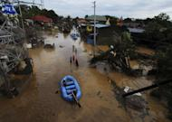 Rescuers paddle their rubber boat to search for survivors following a flash flood that inundated Cagayan de Oro city, Philippines, Saturday, Dec. 17, 2011. A tropical storm triggered flash floods in the southern Philippines, killing scores of people and missing more. Mayor Lawrence Cruz of nearby Iligan said the coast guard and other rescuers were scouring the waters off his coastal city for survivors or bodies that may have been swept to the sea by a swollen river. (AP Photo/Froilan Gallardo)