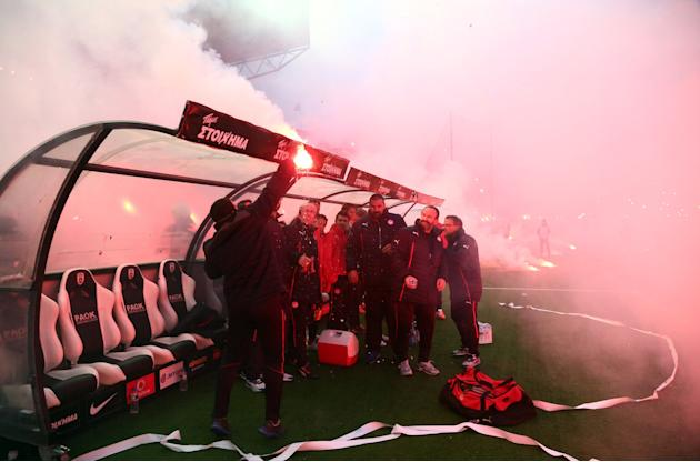 In this Wednesday, April 16, 2014 photo PAOK's fans throw flares, one of this sets on fire the bench, to Olympiakos' team before a semi-final of the Greek Cup in the northern port city of Thes