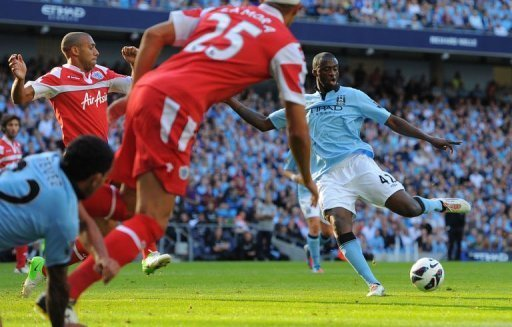 Manchester City's midfielder Yaya Toure (R) scores during their English Premier League football match against Queens Park Rangers at The Etihad stadium in Manchester. Manchester City won 3-1
