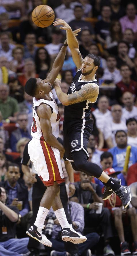 Brooklyn Nets guard Deron Williams, right, passes over Miami Heat guard Norris Cole during the first half of an NBA basketball game, Wednesday, March 12, 2014, in Miami