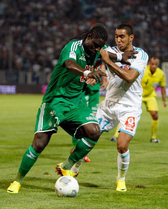 Saint-Etienne's Senegalese defender Moustapha Sall, left, challenges for the ball with Marseille's French forward Dimitri Payet during their League One soccer match at the Velodrome Stadium, in Marsei