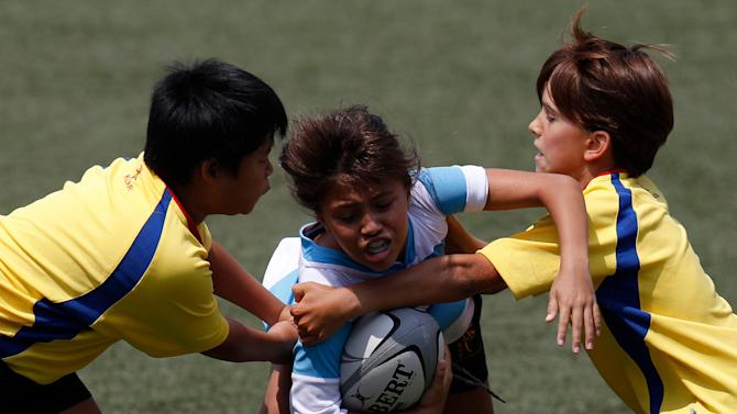 A player (C) from the Argentina representative team is tackled by players of the Romania representative team during the Te Aka Aorere mini-rugby union tournament in Hong Kong on September 10, 2011. The Te Aka Aorere mini-rugby union tournament was organised by the New Zealand consulate general and the Hong Kong rugby football union to mark the start of the 2011 Rugby World Cup in New Zealand. AFP PHOTO / Dale de la Rey (Photo credit should read DALE de la REY/AFP/Getty Images)