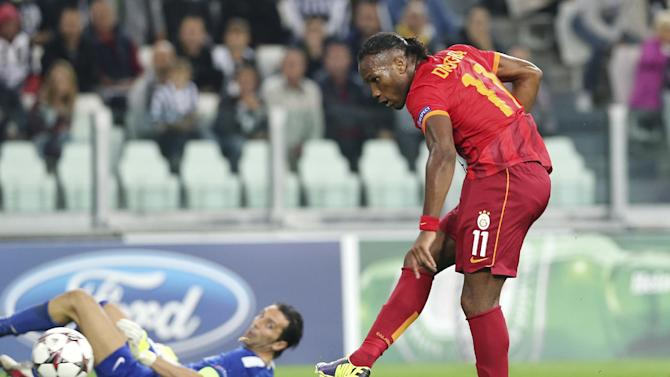 Galatasaray forward Didier Drogba, right, of Ivory Coast, scores past Juventus goalkeeper Gianluigi Buffon during a Champions League, Group B, soccer match at the Juventus stadium in Turin, Italy, Wednesday, Oct. 2, 2013
