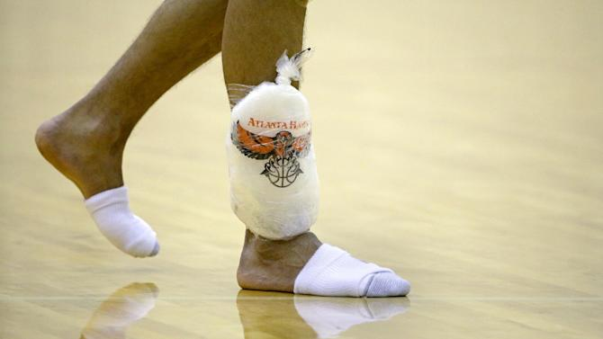 Atlanta Hawks' Gustavo Ayon, of Mexico, walks across the court with ice on his leg as he leaves NBA basketball training camp, Tuesday, Oct. 1, 2013, in Athens, Ga