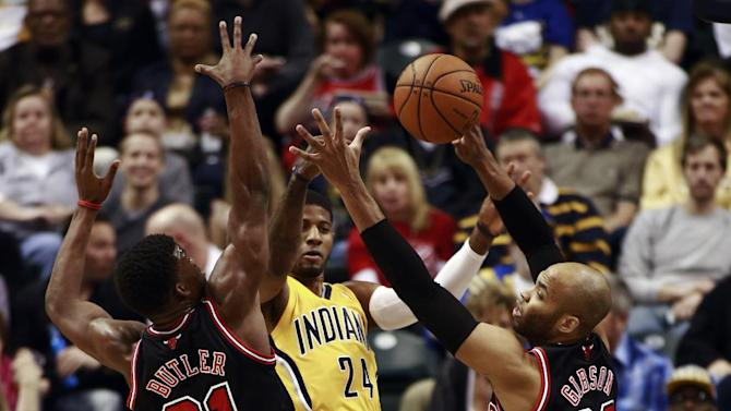 Indiana Pacers forward Paul George (24) passes the basketball between Chicago Bulls guard Jimmy Butler (21) and forward Taj Gibson during the first half of an NBA basketball game in Indianapolis, Friday, March 21, 2014