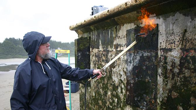 In this Thursday, June 7, 2012 photo proivded by the Oregon Park and Recreations Department, an unidentified worker burns off debris from a dock float torn loose from a Japanese fishing port by the 2011 tsunami that washed up Tuesday on Agate Beach near Newport, Ore. Workers with shovels, rakes and other tools first scraped the structure clean, then briefly used low-pressure torches to sterilize the dock. (AP Photo/Oregon Parks and Recreation Department)