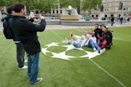 People take photos in a 'football fan zone' at Trafalgar Square in London, on May 22, 2013, a few days ahead of the UEFA Champions League final match between Bayern Munich and Borussia Dortmund, at Wembley