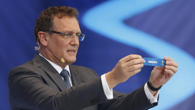 "Valcke holds up the slip showing ""Honduras"" during the draw for the 2014 World Cup in Sao Joao da Mata"