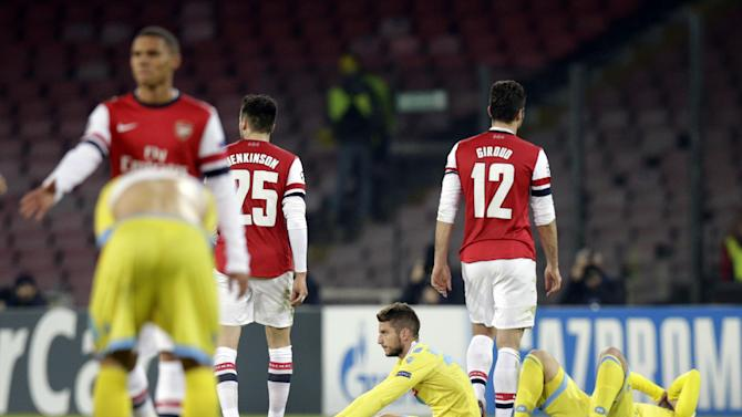Players leave the field at the end of a Champions League, group F soccer match, at the Naples San Paolo stadium, Italy, Wednesday, Dec. 11, 2013. Ten-man Arsenal advanced to the Champions League knockout phase for the 14th consecutive year despite a 2-0 loss Wednesday at Napoli, which was eliminated. Gonzalo Higuain scored in the 73rd minute but the San Paolo stadium was soon silenced when word arrived that Borussia Dortmund had scored a late goal in a 2-1 win at Marseille to win Group F