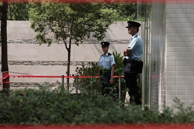 Image taken on October 3, 2012 shows police standing guard outside a cordoned-off building in Hong Kong. The severed heads of a Hong Kong couple were found in a refrigerator in a murder for which their 29-year-old son has been arrested, according to reports