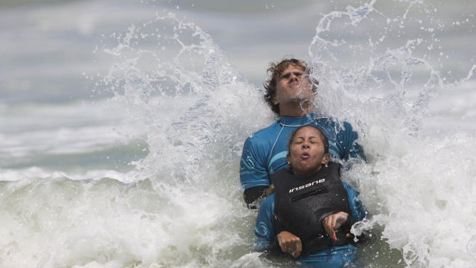 In this March 16, 2013 photo, Monique Oliveira is aided by an AdaptSurf volunteer as a wave breaks at Barra da Tijuca beach in Rio de Janeiro, Brazil. AdaptSurf is a Rio-based non-governmental organization that aims to make beaches accessible to the disabled and encourage them to practice water sports. The organization is the first of its kind in Brazil. (AP Photo/Felipe Dana)