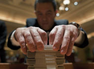 Baccarat dealer Ramiro Nepomuceno, right, shuffles cards while preparing a table for play at the MGM Hotel and Casino, Wednesday, Jan. 25, 2012, in Las Vegas. There are generally more Asian gamblers in Vegas because of the Chinese New Year, and it means increased traffic at high limit baccarat tables. Though not widely known, baccarat is actually the most profitable table game for casinos which try to court Asian gamblers who tie luck and good fortune to the start of the Lunar Year. (AP Photo/Julie Jacobson)