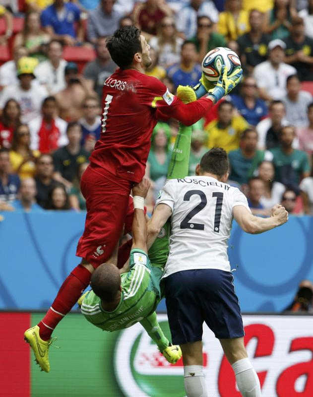 France's goalkeeper Hugo Lloris saves a shot as Nigeria's Peter Odemwingie falls during their 2014 World Cup round of 16 game at the Brasilia ...