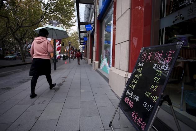 A woman walks past a board showing the length and annual yield rates of finance products, outside a shop in Shanghai, China