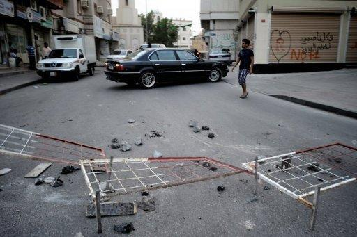 Toppled barricades and rocks littler the street as Bahraini Shiite Muslim protesters clash with riot police