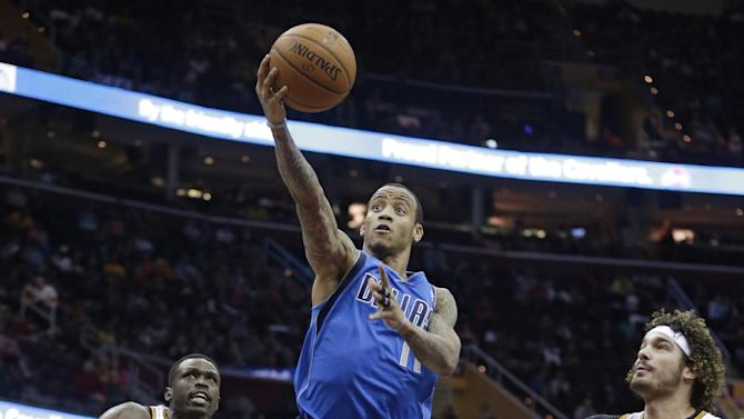 CORRECTS FROM LOUL TO LUOL - Dallas Mavericks' Monta Ellis (11) shoots between Cleveland Cavaliers' Luol Deng, (9) from Sudan, and Cleveland Cavaliers' Anderson Varejao (17), from Brazil, during the first quarter of an NBA basketball game Monday, Jan. 20, 2014, in Cleveland
