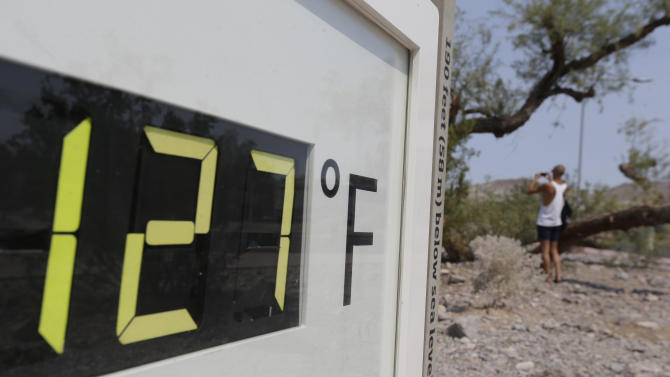 A visitor to the Furnace Creek Vistitor Center walks by a digital thermometer in Death Vally National Park Friday, June 28, 2013 in Furnace Creek, Calif. Excessive heat warnings will continue for much of the Desert Southwest as building high pressure triggers major warming in eastern California, Nevada, and Arizona. (AP Photo/Chris Carlson)