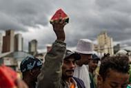 """A homeless man raises a piece of watermelon to thank NGOs and social groups who prepared barbeques and distributed fruits for them during a demonstration against paramilitary police's clean-up operation in the area called """"Cracolandia"""" (Crackland) in downtown of Sao Paulo, Brazil on January 14"""