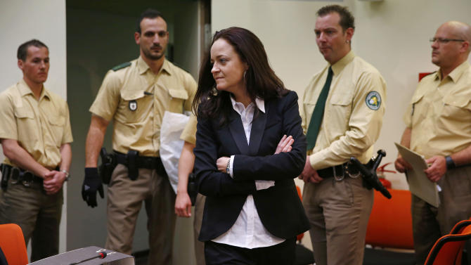 Beate Zschaepe, member of the neo-Nazi group National Socialist Underground (NSU) enters the court room before the start of her trial in Munich, southern Germany, Monday, May 6, 2013. The highest-profile neo-Nazi murder trial in Germany in decades opened Monday amid tight security and intense media interest, with the five accused appearing in public for the first time since their arrest more than a year ago.  Zschaepe, 38, is accused by prosecutor of complicity in the murder of eight Turks, a Greek and a policewoman between 2000 and 2007. If convicted she faces life imprisonment. Zschaepe is also accused of involvement in at least two bombings and 15 bank robberies carried out by her accomplices Uwe Mundlos and Uwe Boenhardt, who died in an apparent murder-suicide in November 2011.  (AP Photo/Matthias Schrader)